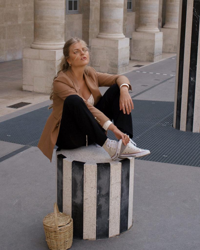 Franziska sitzt auf einer Säule am Palais Royal und trägt einen zeitlosen Blazer