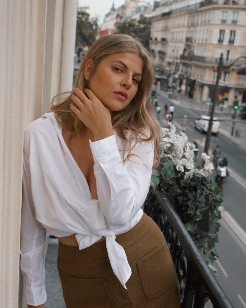 der französische Stil, Franziska trägt eine weiße Hemdbluse auf einer typisch Pariser Balkon