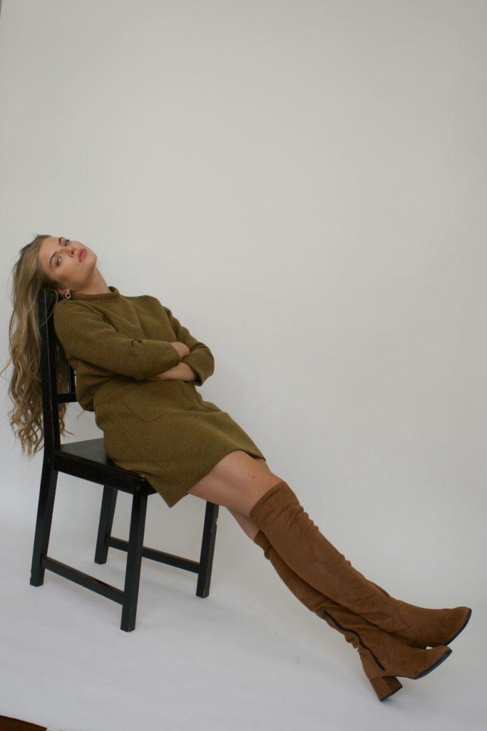 che Schuhe tragen Französinnen im Winter, Knee High Boots zu einem Strickkleid vor einer weißen Leinwand
